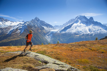 A young male runner on a mountain pasture near Chamonix with the spectacular Mont Blanc range in the background.