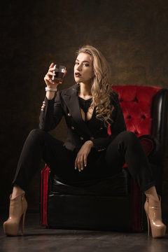 beautiful sexy blonde in a black jacket and underwear on a dark background