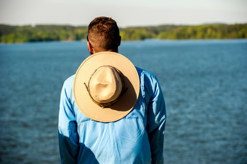 A back view of man looking at a lake with a large hat on his shoulders.