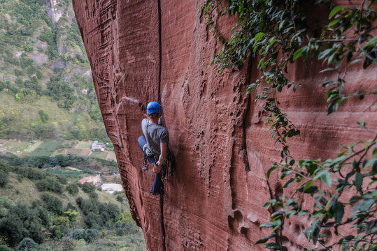 Rock climber climbing cliff, Liming, Yunnan Province, China