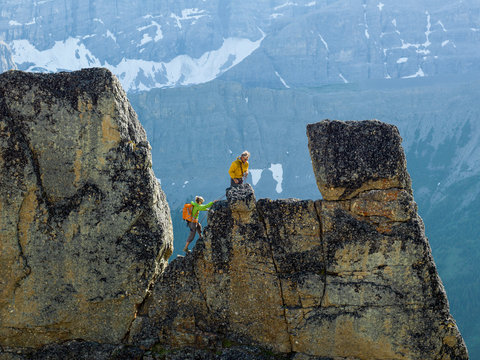 Mountaineering couple ascend rock pinnacle, mountains