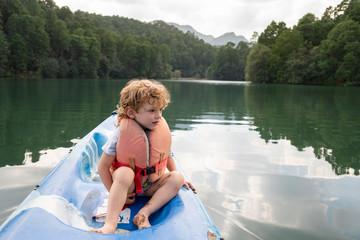 A two years old boy sitting on a kayak at Rancho Santa Elena, Hidalgo, Mexico,