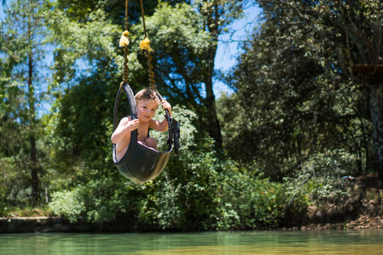 Boy riding zip line over water, Rancho Santa Elena, Hidalgo, Mexico