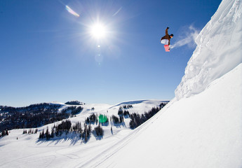Snowboarder Jumping of snow cliff