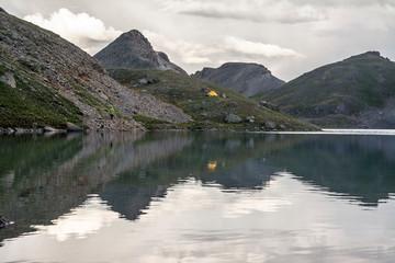 A woman camping near alpine lake, San Juan National Forest,  Silverton, Colorado.