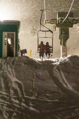 Two girls riding the ski lift while  night skiing, Silverton, Colorado.