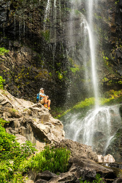 A woman hiking below waterfall, Pagosa Springs, Colorado.