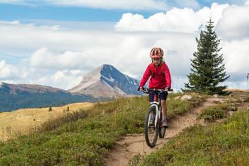A young girl mountain biking in the San Juan National Forest, Silverton, Colorado.