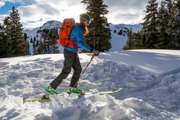 A woman backcountry skiing on Red Mountain Pass, Silverton, Colorado.