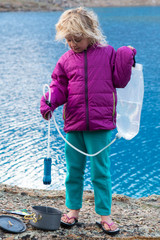 A young girl filtering water near a blue lake, San Juan National Forest,  Silverton, Colorado.