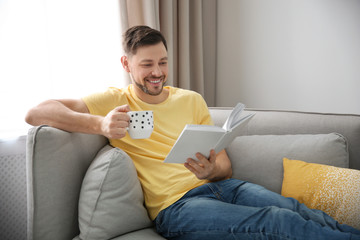 Handsome man with cup of coffee reading book on sofa at home