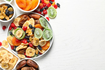 Bowls of different dried fruits on wooden background, top view with space for text. Healthy...