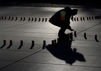 A student arranges candles to commemorate 70 years since the largest Soviet mass deportations in Tallinn