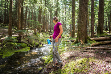 A woman stands beside a small creek in a forest with a water bottle in her head, looking behind her.
