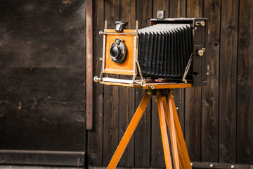An old large format camera on a wooden tripod.
