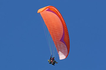 Fototapete - Tandem paraglider flying red wing