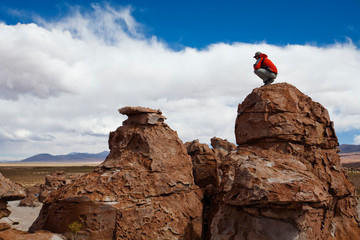 A young man plays on the rocks in the Atacama Desert. The Salar de Uyuni is the world's largest salt flat and home to one of the largest deposits of lithium in the world. The communities surrounding this region could potentially benefit greatly or suffer with the development and extraction.