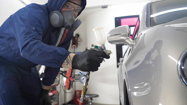 In slow motion, a Man (Man) professional in working uniform with spray guns in his hands and a respirator in protective glasses puts paint (ceramics) on the car on different parts of the car.