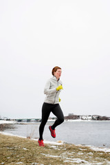 Woman running on trail against clear sky