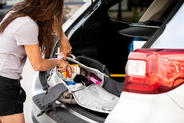 Woman packing bag in trunk of car