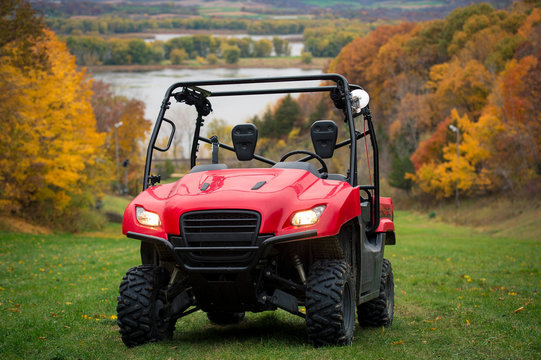 Side by side Atv vehicle on grass trail in the fall along Mississippi River