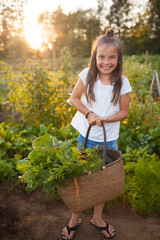 Girl holding basket full of fresh vegetables in garden