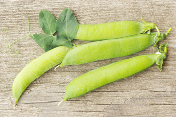fresh green peas on wooden background
