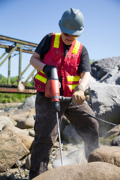 A woman uses a hammer drill on a large boulder.
