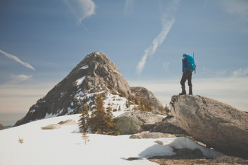 Hiker looking at view while standing on a rock on the mountain in winter