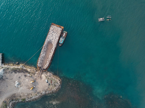 Aerial view of large barge with stones near Sumbawa island coastline