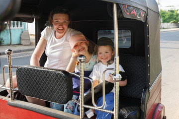 Family on vacation, mother and kids sitting in tuk-tuk, having fun.