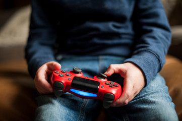 Boy moving buttons on video game controller while playing video game