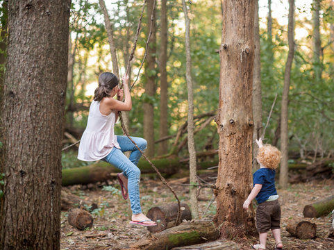 Brother and sister playing on rope swing in the woods in a park