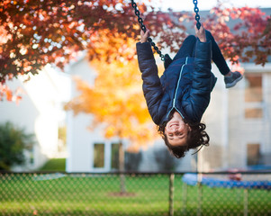 Girl swinging upside down in backyard with happy expression