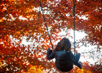 Young girl swinging high into the autumn leaves