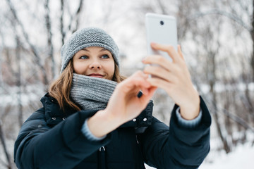 Smiling young woman getting a selfie on her phone in winter park