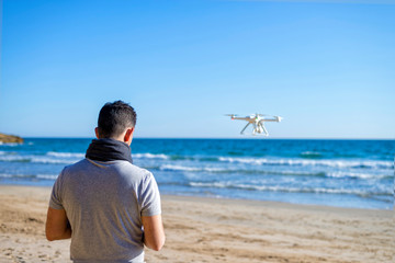 Rear view of a Man on a beach testing its drone and recording v