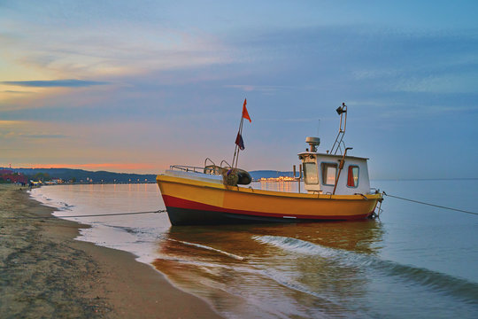 Picturesque landscape of a sunset with a fishing boat on beach in Sopot, Poland.
