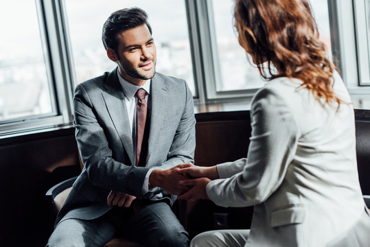 selective focus of handsome businessman shaking hands with businesswoman