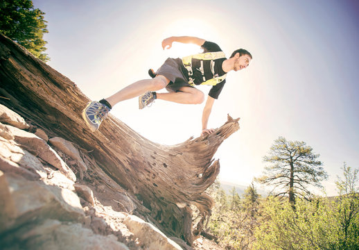 Trail Runner Jumps over a log in Durango Colorado