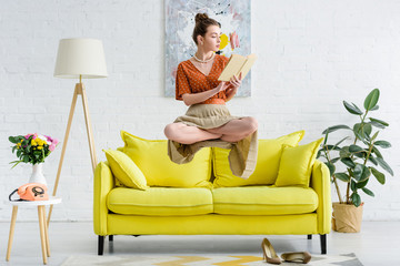 elegant young woman in lotus pose levitating in air while reading book in living room Wall mural