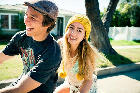 Young couple riding bike through neighborhood