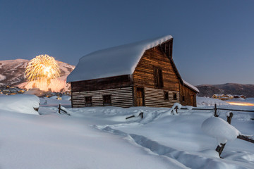 Barn in winter and New Year firework display in background, Steamboat Springs, Colorado, USA