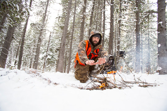A male hunter warming his hands over fire during winter
