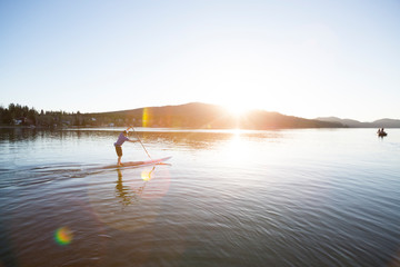 A fit male stand up paddle boards (SUP) at sunset on Whitefish Lake in Whitefish, Montana.