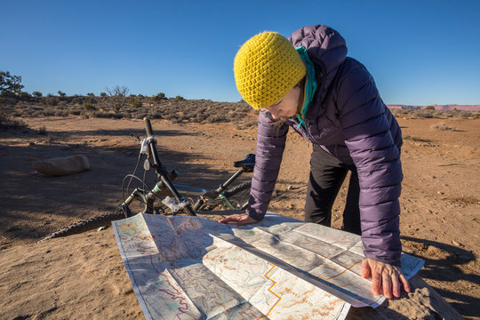 Woman reading map while on bicycle trip in Canyonlands National Park, Moab, Utah, USA