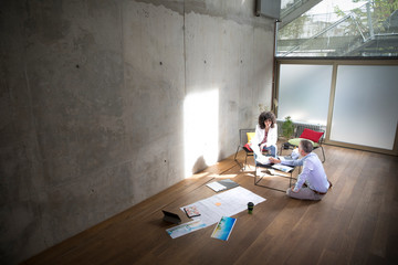 Businessman and businesswoman talking in a loft with documents on the floor