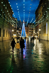Spain, Gijon, back view of mother and two children walking at pedestrian area in the evening at Christmas time