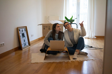 Young women sitting on floor of their new home, using laptop