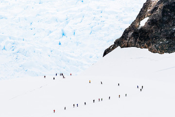Hikers on mountainside in snow, Paradise Harbor, Antarctica